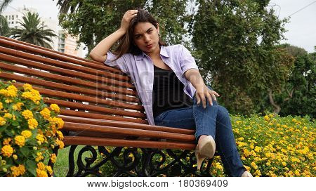 Unhappy Or Serious Teen Girl Sitting On Park Bench