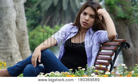 Unhappy Serious Girl Sitting on a Park Bench