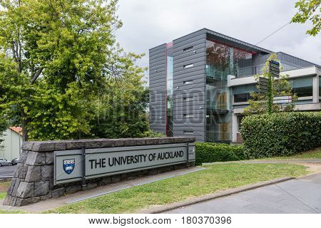 Auckland New Zealand - March 1 2017: Sign and logo of University of Auckland set near modern dark gray offices in green park like environment. Gray sky.