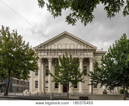 Auckland New Zealand - March 1 2017: Greek-Roman architecture for beige facade with triangular frieze of Baptist Tabernacle in Queen Street. Green vegetation and line of pillars.