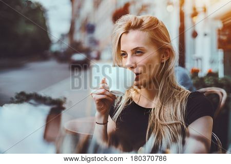Beautiful adult blonde woman drinking enjoying delicious hot tea and thoughtfully looking outside while sitting in street cafe alone on sunny summer evening after hard work day