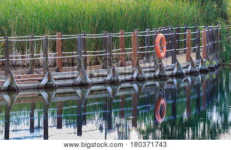 Serene floating boardwalk with orange life preserver reflected in water