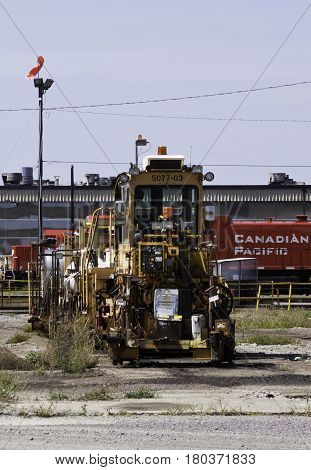 Montreal, Quebec, August 20, 2016 - Close up view of an old railroad work vehicles with a red locomotive in the background in the CP Rail Train Yards in Cote Saint Luc in Montreal, Quebec on a sunny day in August.