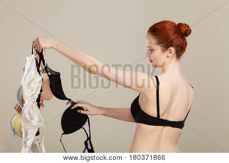 Bosom concept. Slim attractive red hair woman wearing black underwear holding many bras in hand choosing witch bra to wear