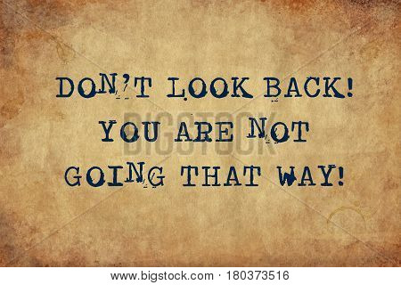 Inspiring motivation quote with typewriter text don't look back you are not going that way. Distressed Old Paper with Typing image.