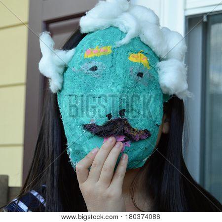 little girl black hair behind blue paper mache mask