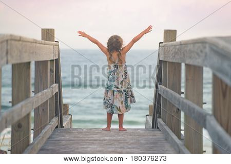 Little girl standing with open arms near the ocean on wooden bridge, feeling immensity of ocean, embracing nature.