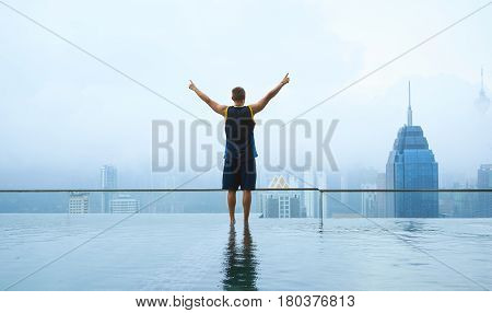 Young guy stand on swimming pool on roof top with beautiful city skyline viewearly morning with mist .