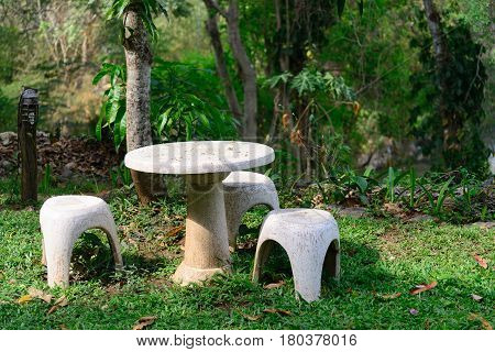 Garden Seat Of Stone Or Stone Table And Benches  In The Garden.