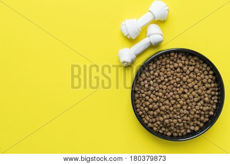 Dog bones and dog food on yellow background