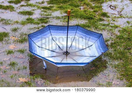 Umbrella taken by the wind and landed upside down in a big spring puddle during a rain storm bad day or spring concept