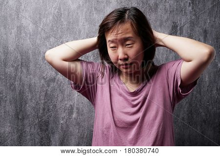 Portrait of young asian woman with sleepy face over the dark texture background.