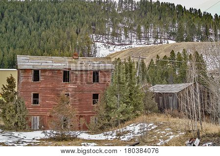 Abandoned buildings in a rural area with a bit of snow and lots of trees