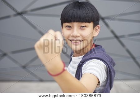 Portrait Of Cool Asian Kid Posing & Smiling Outdoors
