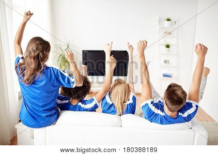 friendship, leisure, sport, people and entertainment concept - happy friends or football fans watching soccer on tv and celebrating victory at home
