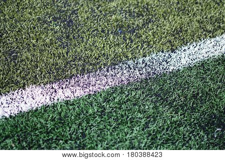 White line marked on football field made of artificial turf