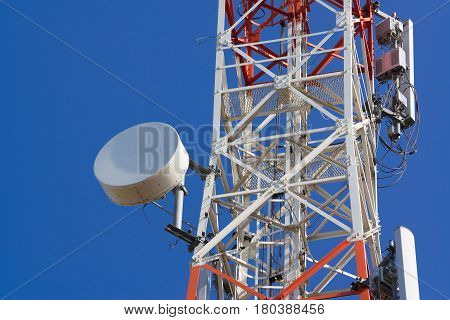 Mobile phone communication antenna tower with satellite dish on blue sky background Telecommunication tower