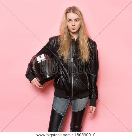 Biker girl wearing black leather jacket holding motorcycle helmet.