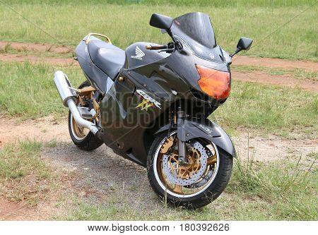 Parked Black Honda Cbr1100Xx Motorbike On Green Grass