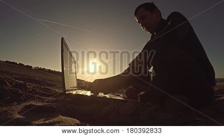 man businessman freelancer laptop working behind sitting on beach freelancing silhouette in sun