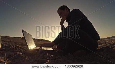 businessman man freelancer working behind sitting on beach laptop freelancing silhouette in sun