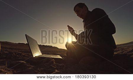 businessman man freelancer working behind sitting on beach freelancing laptop silhouette in sun