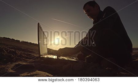 man businessman freelancer working laptop behind sitting on beach freelancing silhouette in sun