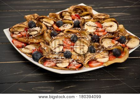 Homemade russian pancakes with banana blueberries strawberries and nutella.
