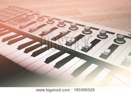 Midi keyboard close-up keys and faders. Toned