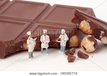 Miniature people: A chef and cooks in front of a chocolate bar
