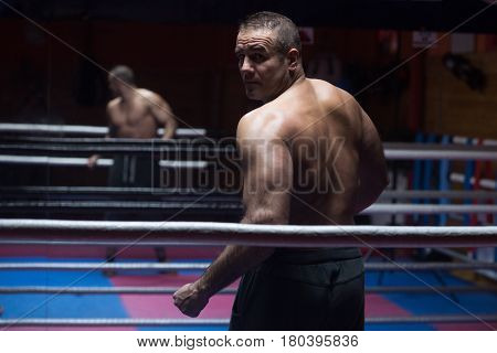 portrait from the back of muscular professional kickboxer who standing in the ring while training for the fight