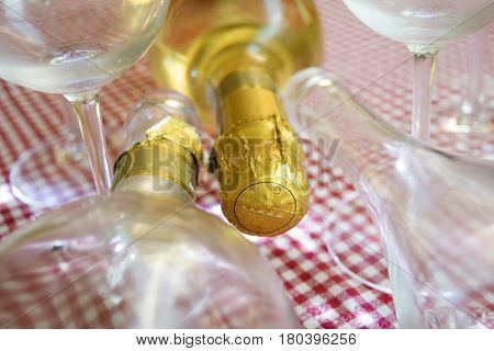 detail of the neck of a champagne bottle surrounded from crystal glasses