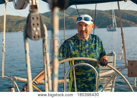 Man at helm leads a sailing yacht in the sea.