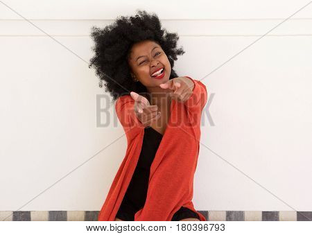 Cheerful Young African Woman Pointing Fingers And Winking
