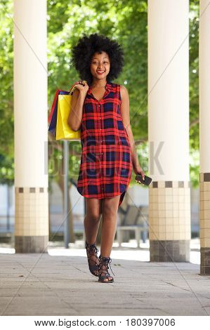 African Woman Walking With Shopping Bags And Mobile Phone