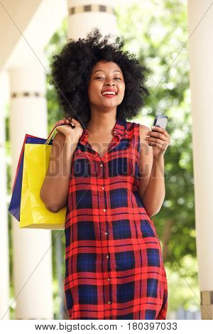 Happy African Woman With Shopping Bags And Cellphone Outside
