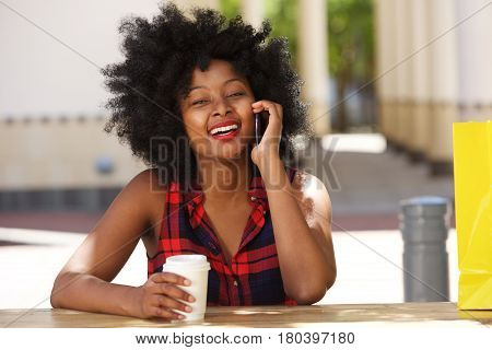 Smiling African Woman On Cellphone With Coffee Outside