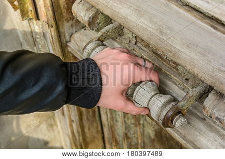 Closeup photo of male hand opening obsolete wooden door with massive handle