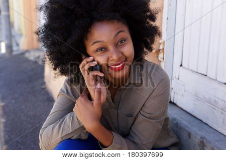 Happy Woman Sitting Outside On Mobile Phone Call
