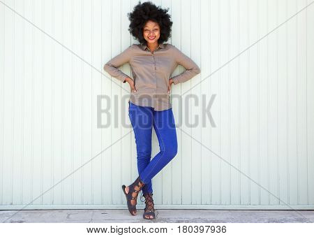 Full Length Happy Woman Standing By White Wall With Confidence