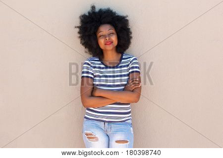 Beautiful Young Black Woman Standing With Arms Crossed By Wall