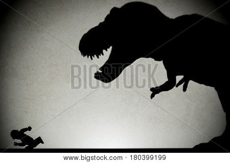 shadow of tyrannosaurus chasing human on wall