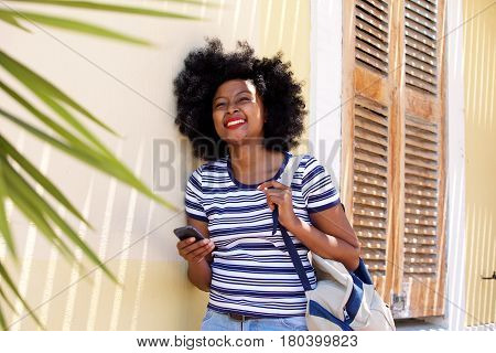 Smiling Woman With Cellphone Standing Outside House