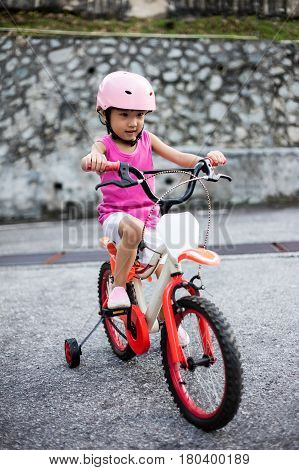 Asian Chinese Little Girl Riding Bicycle On Tar Road