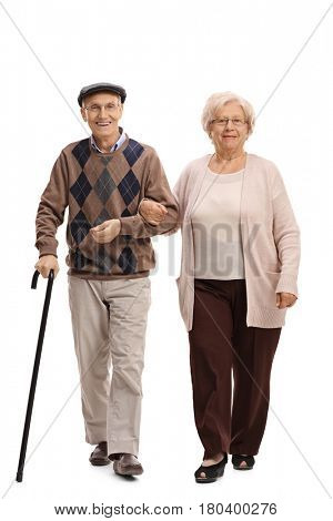 Full length portrait of an elderly man and woman walking towards the camera isolated on white background