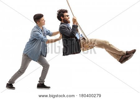 Full length profile shot of a son pushing his father on a swing isolated on white background