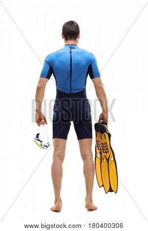 Full length rear view shot of a man in a wetsuit holding a diving mask and swimming fins isolated on white background