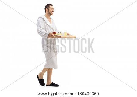 Full length profile shot of a guy in a bathrobe walking and carrying a tray with breakfast isolated on white background