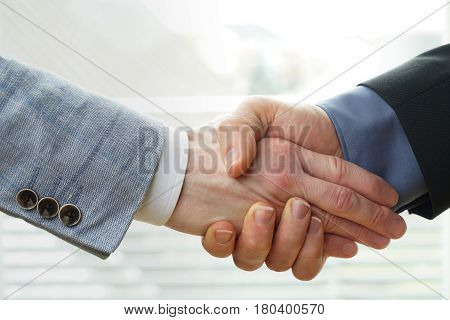 businessman crushes the hand of another businessman - concept for dominance, negotiation