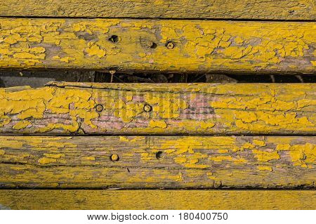 Texture of obsolete weathered wooden planks with some spaces between them and cracked yellow paint